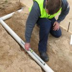 Professional Plumber Laying Underground Pipe